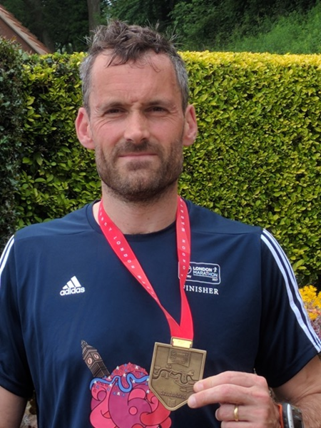 Paul Hutton represents FOAG in the 2017 London Marathon  - Paul in his Finisher Tee Shirt and with Finisher Medal